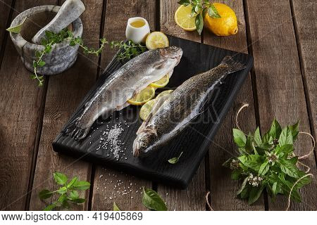 Two Lemon Stuffed Raw Trout And Condiments On Wooden Background
