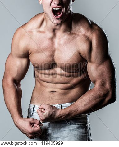 Screaming Man With Well Trained Body, Biceps, Abs And Pecs And Wearing. Muscular Male Strains Muscle