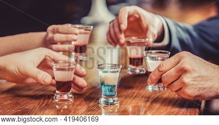 Group Friends Tequila Shot Glasses In Bar. Male Hands Glasses Of Shot Or Liqueur. Friends Drink Shot