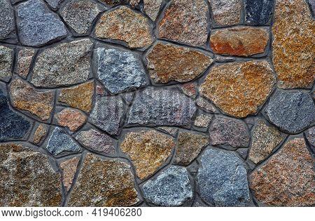 Stone Wall. Wall Of Granite Blocks. A Masonry Wall Of Multicolored Stones Or Blocks Close Up