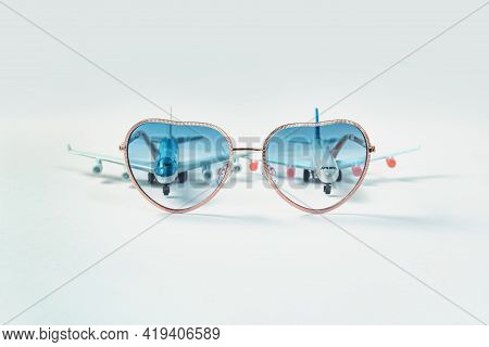 Air Flights And Travel. Two Toy Airplanes Behind Heart Shaped Sunglasses. Copy Space For Air Travel