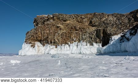 A Picturesque Granite Rock, Devoid Of Vegetation, Against The Backdrop Of A Blue Sky. There Are Crac