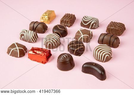 Various Chocolate Pralines On Pink Background. Collection Chocolates Candy. Assorted Chocolates On P