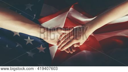 Patriotic holidays. The USA are celebrating 4th of July or Memorial Day. American flag and hands close up.