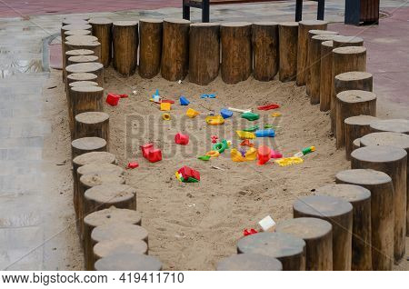 Empty Children's Sandbox Fenced With Vertical Round Logs. Wet Sandbox With Colorful Plastic Toys Aft