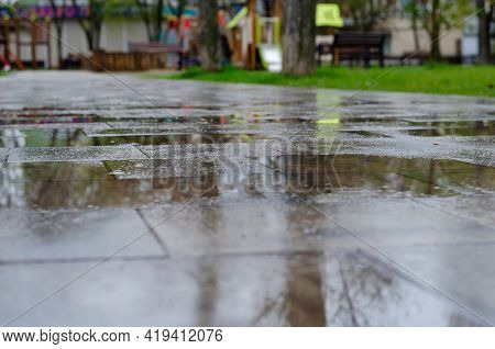 Close-up Of A Puddle On A Path On A Blurred Background Of A City Park An Empty Path In The Park Afte