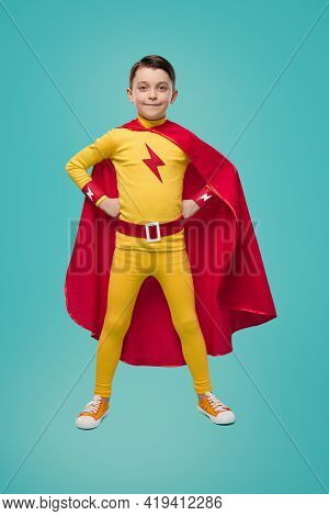 Full Body Of Determined Brave Boy In Red And Yellow Superhero Costume Keeping Hands On Waist And Loo