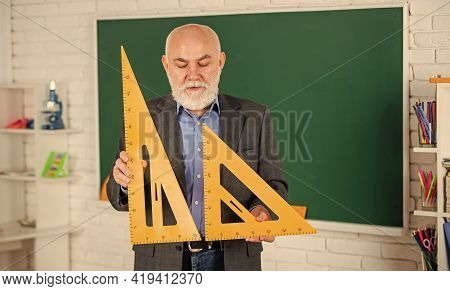 Maths Exam. Mathematics At Chalkboard. Senior Man Teacher Use Math Triangle Tool. Bearded Tutor Man
