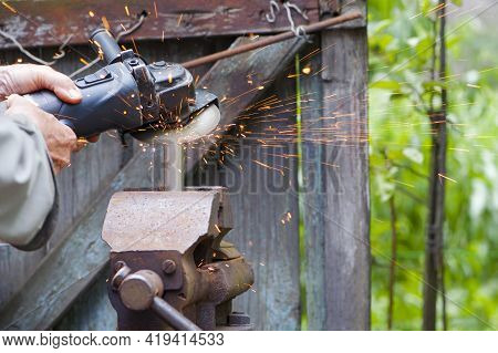 The Worker Cuts Metal, Steel With A Grinder. The Pipe Is Clamped In A Vice, Sparks Fly. Close-up, Th