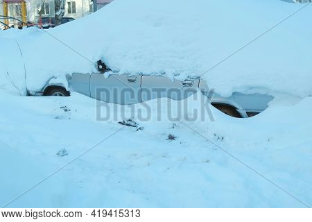 Car Covered By Snow After A Snow Blizzard In Parking Near Residential Building.