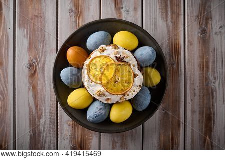 Homemade Easter Cake And Multi-colored Painted Eggs On Black Platter Against A Background Of Texture