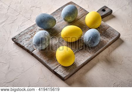 Homemade Easter Colored Yellow And Grey Marble Eggs On Wooden Aged Cutting Board. Close Up, Selectiv