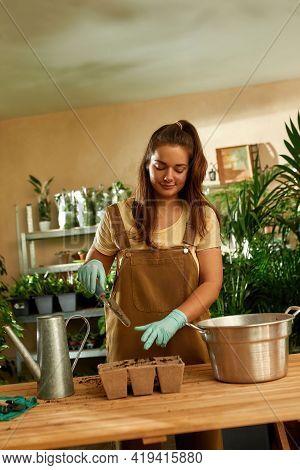 Young Girl Working In The Home Garden. Home Garden Concept. Uniformed Gardener Standing At His Desk