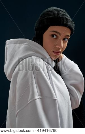 Portrait Of Cute Young Arabian Girl In Hoodie Posing On Dark Background And Looking To Side, Vertica