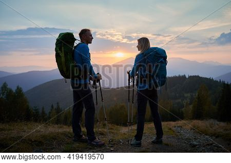 Full Length Of Young Man And Woman Hikers Holding Trekking Poles And Chatting While Hiking Together
