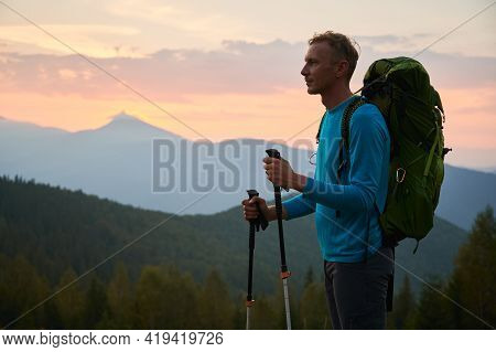 Side View Of Male Traveler Stopping While Hiking And Watching Into The Distance, Thinking About The
