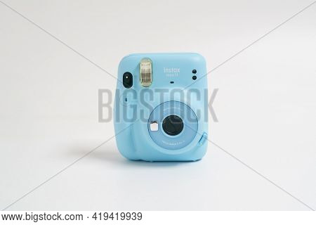 BERLIN, GERMANY- OCTOBER 30, 2020: The blue turquoise Fujifilm Instax mini 11 instant camera on background.