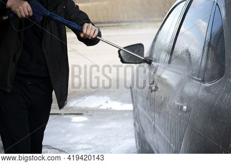 A Worker At A Car Wash Washes A Gray Car With A Jet Of Water. Manual Car Wash With Pressurized Water