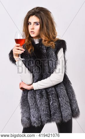 Luxury Winery Concept. Fashion Model Long Hair Fur Coat Or Vest Hold Wineglass. Fashionable Lady Lik