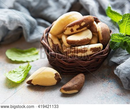 Basket With Brazil Nuts On Grey Concrete Table