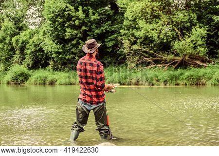 Hobby And Sport Activity. Pothunter. Fisherman With Fishing Rod. Mature Man Fly Fishing. Man Catchin
