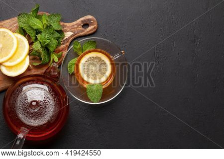 Herbal tea with mint and lemon. Tea cup and teapot on stone table. Top view flat lay with copy space