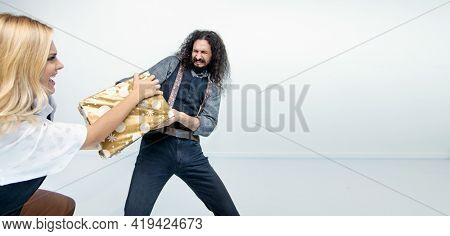 Young weird couple on white background, posing with christmas gift