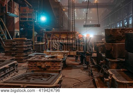 Workers In Helmets And Face Masks Works With Mold On Crane Chains After Metal Casting In Steel Mill