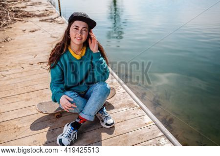 A Young Caucasian Hipster Woman Sits Cross-legged On A Skateboard And Smiles. In The Background-the