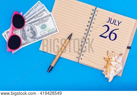 26th Day Of July. Travel Concept Flat Lay - Notepad With The Date Of 26 July Pen, Glasses, Dollars A