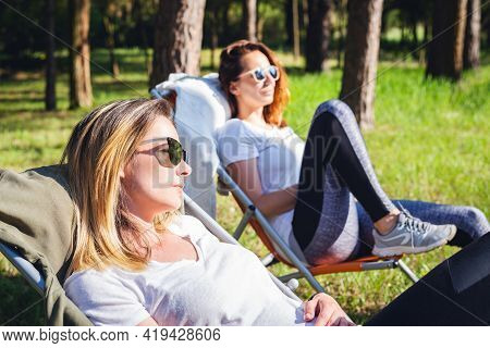 Two Beautiful Woman Relaxing In Nature. Happy People Lifestyle. Women In Forest Nature. Nature Lifes