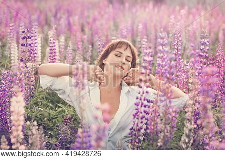 Young Woman In Sprawling White Shirt Is Pulled In Lupin Colours In Summer