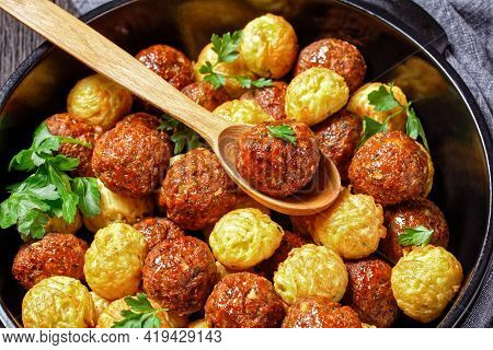 Meatballs And Spaghetti Balls Baked On A Black Baking Dish - Italian Cuisine, Served On A Dark Woode