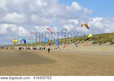 Noordwijk, The Netherland - May 2, 2021: Paraglider's Soaring Above Dutch Dikes In The City Of Noord