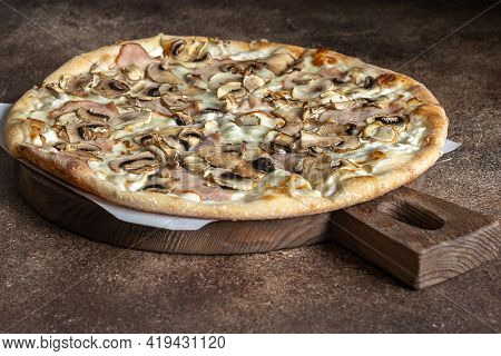 Thin Crust Pizza With Mushrooms And Ham On The Wooden Board On Dark Brown Background