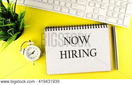 Now Hiring Text On Notebook With Keyboard , Pen And Alarm Clock On Yellow Background