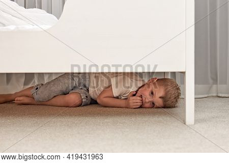 A Frightened Little Boy Hides Under A Childs Bed. Concepts Of The Problem Of Domestic Violence