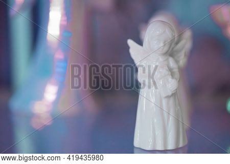 Small White Marble Figurine Of An Angel In Dress On A Pearlescent Pink Blue Blurred Bokeh Background