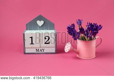 Calendar For May 12: A Cube With The Number 12, The Name Of The Month Of May In English,a Pink Water