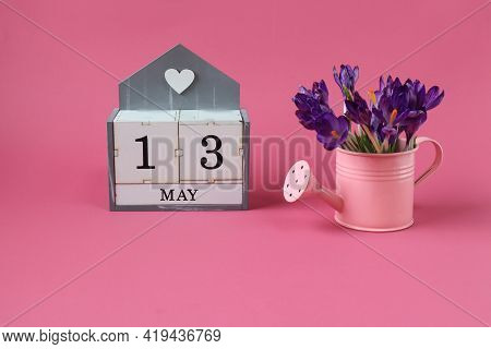 Calendar For May 13: A Cube With The Number 13, The Name Of The Month Of May In English,a Pink Water