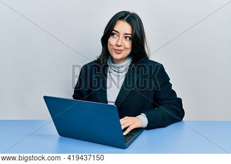 Beautiful hispanic woman working at the office with laptop smiling looking to the side and staring away thinking.