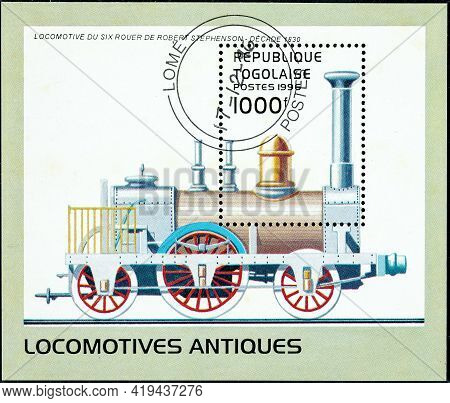 Togo - Circa 1996: A Stamp Printed In Togo Shows An Old Robert Stephenson Six-wheel Locomotive From