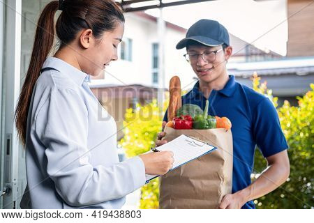 Asian Woman Customer Order Food Delivery Online And Standing In Front Of The House To Receive Grocer