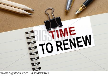 Time To Renew . The Inscription On The Business Card Is Attached To The Notebook.