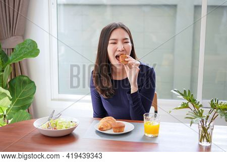 Young Asian Woman Eating Bread With A Glass Of Fresh Orange Juice And Healthy Salad While Breakfast