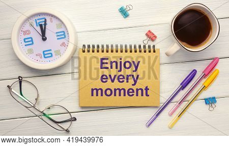 Enjoy Every Moment - An Inscription On A Notebook On A Table With A Clock And Office Supplies. Busin