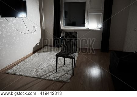 Dark Room Lit By Flash Of Light With One Chair In The Middle. The Concept Of Predicament, Insomnia,