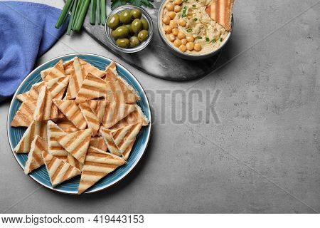 Delicious Pita Chips With Creamy Hummus Served On Grey Table, Flat Lay. Space For Text