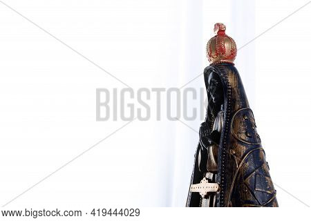 Statue Of The Image Of Our Lady Of Aparecida, Profile View On White Fabric Background