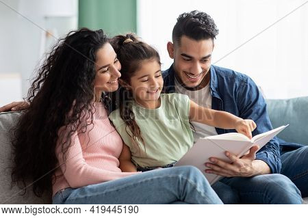 Parenting Concept. Happy Young Arab Parents Reading Book With Their Child